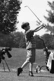 男孩打高尔夫球 免版税图库摄影