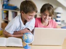 男孩执行女孩他们家庭作业的膝上型计算机 图库摄影
