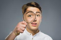 男孩把放大镜,看与在灰色的放大器透镜的孩子眼睛进行下去 免版税库存照片