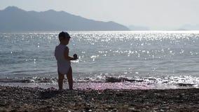 男孩投掷小卵石入从太阳,慢动作的精采海水 股票录像