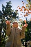 男孩投掷的叶子 免版税库存图片