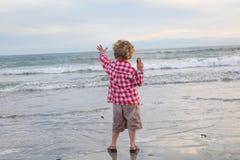 年轻男孩投掷的岩石到海浪里 库存图片