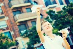 男孩投掷的纸飞机 免版税库存图片