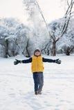男孩投掷雪并且涂他的胳膊对边 库存图片