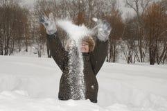 男孩投掷雪 免版税库存图片