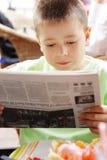 男孩报纸读取 免版税库存图片