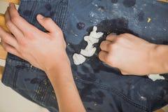 男孩抹在他的裤子的油漆 蓝色牛仔裤和运动鞋弄脏与黄色油漆 顶视图 库存图片