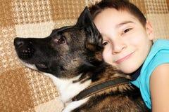 男孩拥抱他的狗 友谊 免版税库存图片