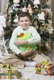 男孩拥抱圣诞节礼物 免版税库存照片
