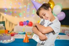男孩拥抱在生日聚会期间的礼物盒 免版税库存图片