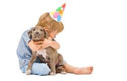 男孩拥抱小狗pitbull 免版税库存照片