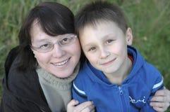 男孩拥抱母亲户外smilin年轻人 免版税图库摄影