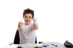 男孩拿着一个电灯泡和一个3D印刷品原型,当做homew时 库存图片