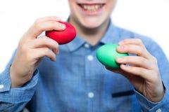 男孩拿着一个红色和绿色鸡蛋 复活节彩蛋 准备的假日 特写镜头 库存照片