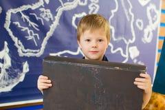 男孩拿着一本书 标签的黑暗的盖子 免版税库存照片