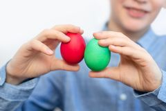 男孩拿着五颜六色的鸡蛋 绿色和红色鸡蛋在男孩的手上 库存照片