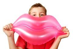 男孩拿着可膨胀的嘴唇桃红色玩具 免版税库存照片