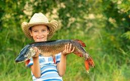 男孩拿着大鱼 免版税库存图片