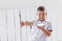 男孩拿着奶油和匙子 免版税库存图片