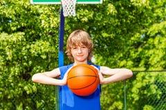 男孩拿着球单独在篮球比赛期间 免版税库存照片