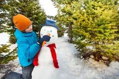 男孩拿着红萝卜投入作为雪人的鼻子 库存图片