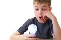 男孩拿着闪亮指示查找插件 免版税图库摄影