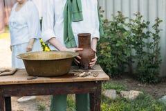 男孩拿着黏土水罐,倾吐水在它外面入一个铜水池 帮助 在背景中是一名年长妇女 免版税库存照片