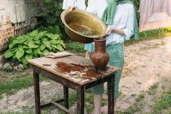 男孩拿着黏土水罐,倾吐水在它外面入一个铜水池 帮助 库存图片