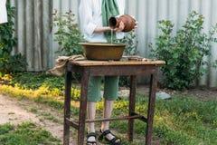 男孩拿着黏土水罐,倾吐水在它外面入一个铜水池 帮助 免版税库存图片