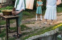 男孩拿着黏土水罐,倾吐水在它外面入一个铜水池 帮助 在背景中是一名年长妇女,并且女孩,垂悬 图库摄影