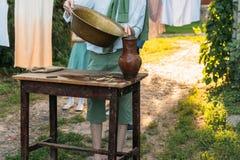 男孩拿着黏土水罐,倾吐水在它外面入一个铜水池 帮助 免版税库存照片