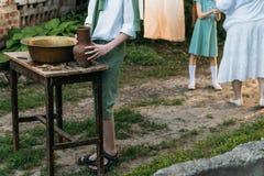 男孩拿着黏土水罐,倾吐水在它外面入一个铜水池 帮助 在背景中是一名年长妇女,并且女孩,垂悬 库存照片