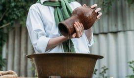 男孩拿着黏土水罐,倾吐水在它外面入一个铜水池 帮助 库存照片