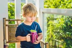 男孩拿着从龙果子的圆滑的人与一片薄荷的叶子和一根吸管 免版税库存图片