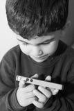 男孩拿着celular电话 库存照片