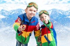 男孩挡雪板的两个兄弟明亮的滑雪夹克衫和风镜的在山滑雪 免版税图库摄影