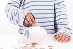 男孩挽救金钱在存钱罐中 库存图片