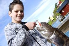 男孩捕鱼战利品 库存图片