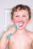男孩掠过的牙和笑,杂乱牙膏 免版税库存图片