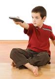 男孩控制少许远程电视 免版税库存图片