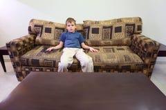 男孩控制远程空间坐的沙发 图库摄影