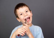 男孩握在钳子的一颗失去的牙 免版税库存照片