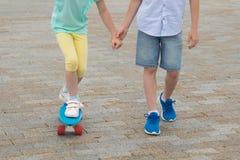 男孩握女孩手,教滑冰在体育委员会,腿特写镜头,在石块背景  免版税库存图片