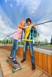 男孩握女孩的手,教骑马滑板 免版税图库摄影