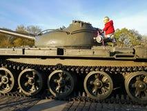 男孩攀登一辆军事坦克的装甲 免版税库存图片