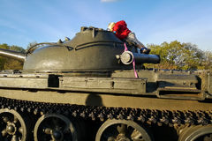 男孩攀登一辆军事坦克的装甲 免版税图库摄影