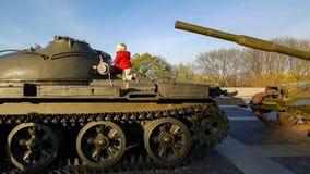 男孩攀登一辆军事坦克的装甲 图库摄影