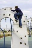 男孩攀登操场设备 免版税图库摄影