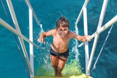 年轻男孩攀登从海的台阶 免版税库存照片