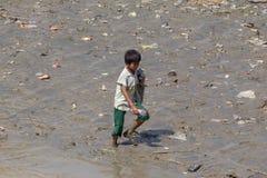 男孩收集在仰光河,缅甸的河岸的塑料瓶 免版税库存图片